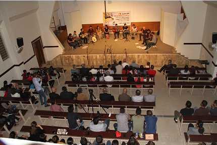 عازف إيطالي مع فريق مشختي المتجول يعزفون للسلام في قضاء الحمدانية